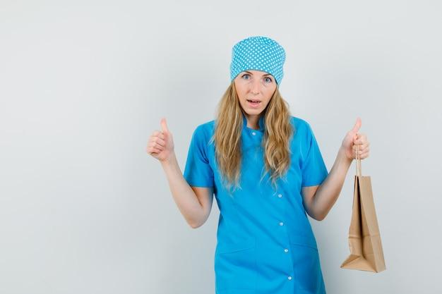 Женщина-врач в синей форме держит бумажный пакет с большим пальцем вверх