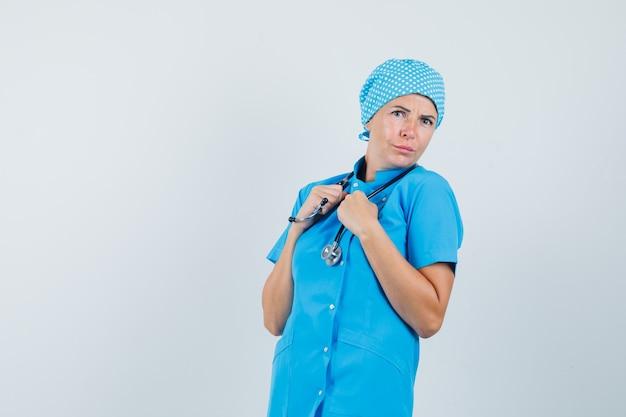 聴診器を保持し、混乱しているように見える青い制服を着た女性医師、正面図。