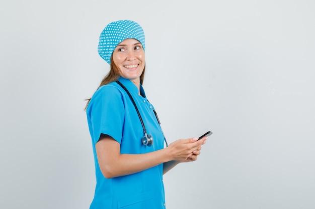 Женщина-врач в синей форме, глядя, держа смартфон и выглядя счастливой.