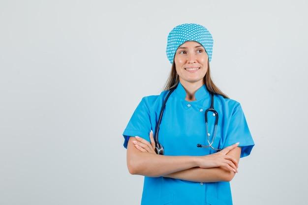 腕を組んで目をそらし、希望に満ちた青い制服を着た女性医師