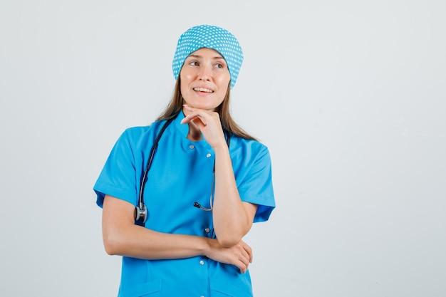 あごに手を当てて目をそらし、希望に満ちた青い制服を着た女医