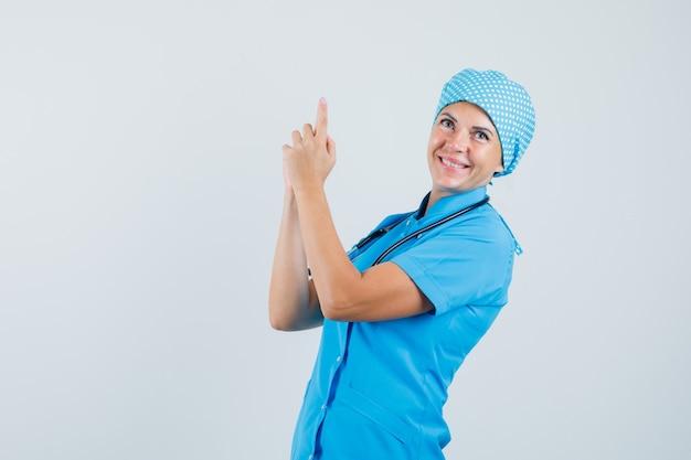 青い制服を着た女医が指ピストルサインを作って陽気に見える、正面図。