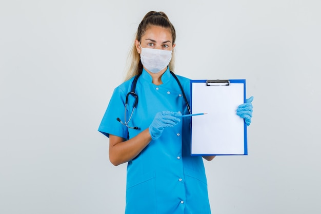 파란색 유니폼, 마스크, 장갑 클립 보드에서 연필을 가리키고 심각한 찾고 여성 의사