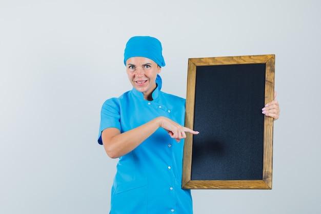 파란색 제복을 입은 여성 의사가 칠판을 가리키고 쾌활한, 전면보기를 찾고 있습니다.