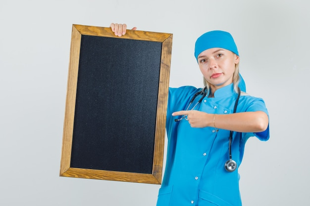 黒板に指を指し、前向きに見える青い制服を着た女性医師
