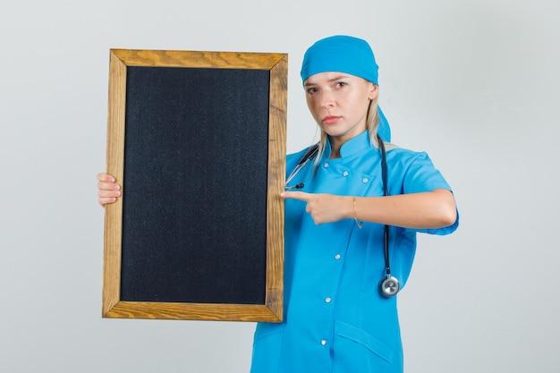 파란색 유니폼 칠판에 손가락을 가리키고 심각한 찾고 여성 의사