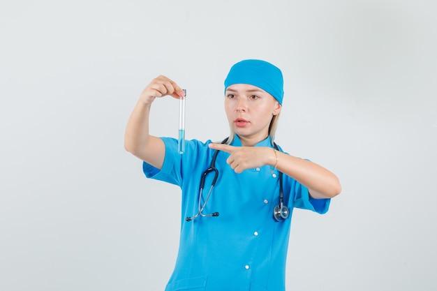 試験管で青い制服人差し指の女医