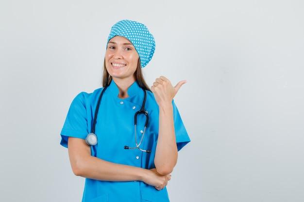 青い制服を着た女性医師が親指を横に向けて喜んでいる