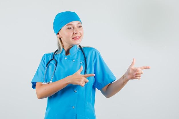 青い制服を着た女性医師が銃のジェスチャーで横を指して陽気に見える