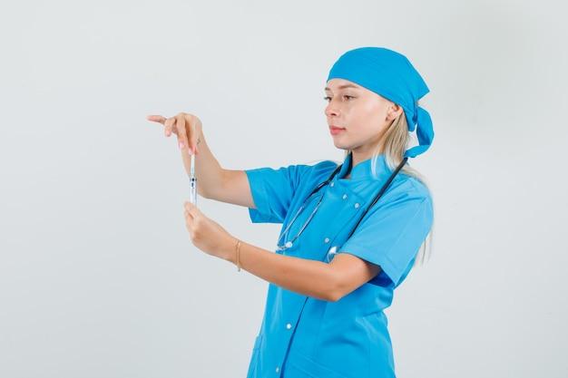 注射器を準備する青い制服を着た女性医師