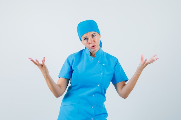파란색 제복을 입은 여성 의사가 질문하는 방식으로 손을 제기하고 의아해하고, 전면보기를 찾고 있습니다.