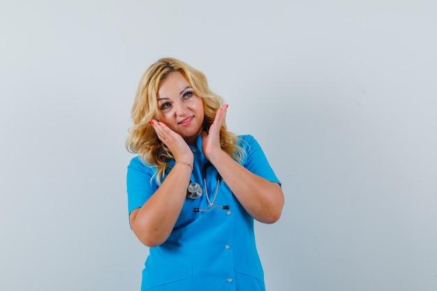 Женщина-врач в синей форме поднимает руки к лицу и смотрит сосредоточенно