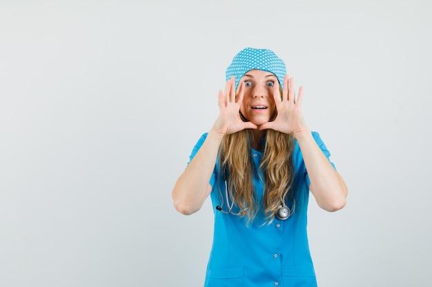 Женщина-врач в синей форме кричит или рассказывает секрет и выглядит нетерпеливой
