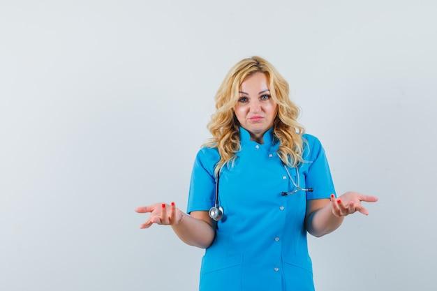 無力なジェスチャーを示し、不安そうに見える青い制服を着た女医