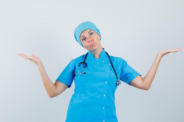 Женщина-врач в синей форме показывает беспомощный жест и выглядит смущенным, вид спереди.