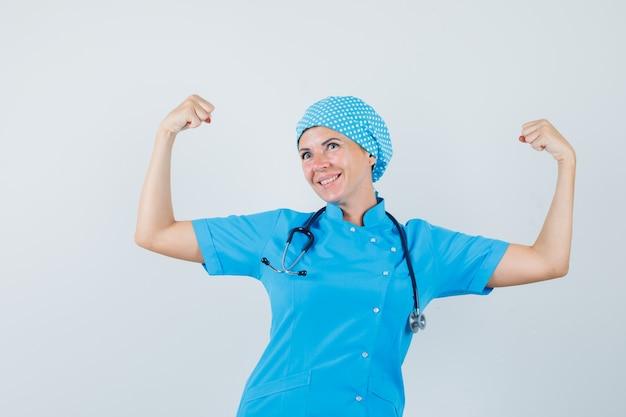팔의 근육을 보여주는 파란색 제복을 입은 여성 의사와 자신감, 전면보기를 찾고.