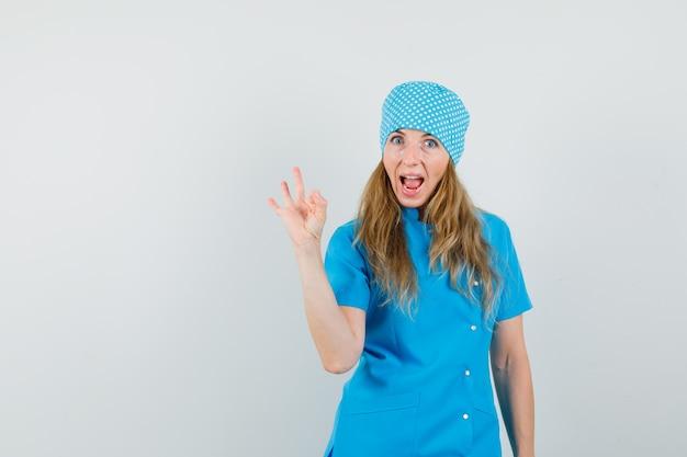 青い制服を着た女性医師がokのしぐさを示し、幸せそうに見えて