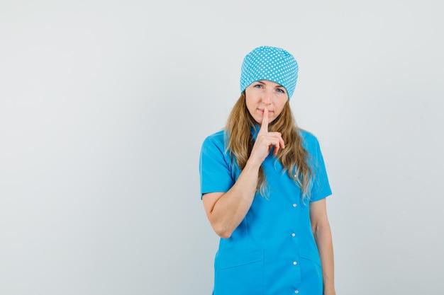 沈黙のジェスチャーを示し、注意深く見て青い制服を着た女性医師