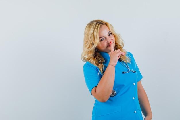 沈黙のジェスチャーを示し、テキストのための自信を持ってスペースを探している青い制服を着た女性医師