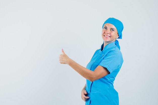 파란색 유니폼 엄지 손가락을 표시 하 고 즐거운, 전면보기를 찾고 여성 의사.