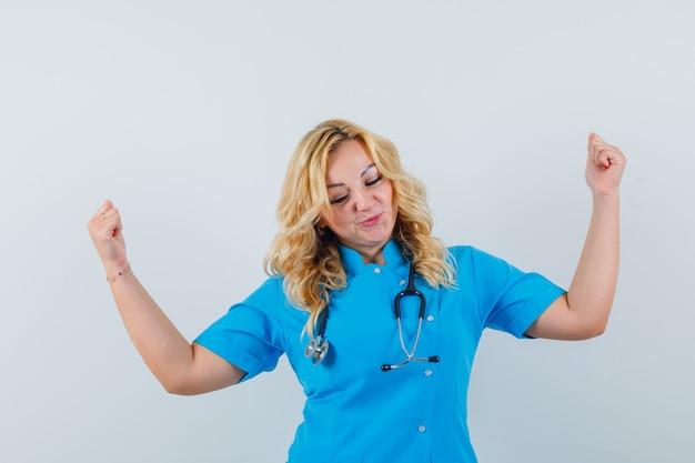 勝者のジェスチャーを示し、幸せそうに見える青い制服を着た女性医師