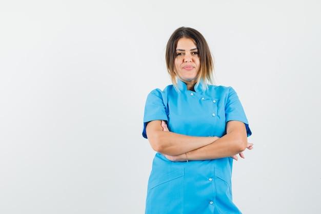 腕を組んで立って自信を持って見える青い制服を着た女医。