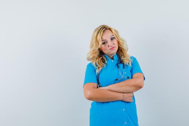 腕を組んで立って不満そうな青い制服を着た女医、