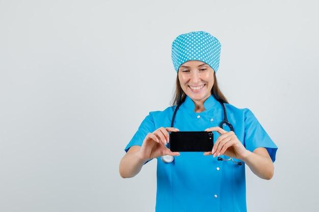 Женщина-врач в синей форме фотографирует на смартфоне и выглядит весело