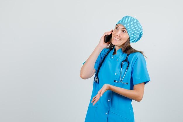 Женщина-врач в синей форме разговаривает по смартфону и улыбается