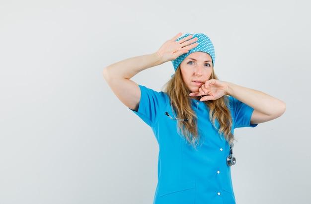 手で顔と頭に触れる青い制服を着た女医