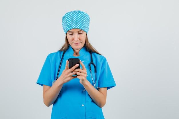 Женщина-врач в синей форме с помощью смартфона и выглядит занятой