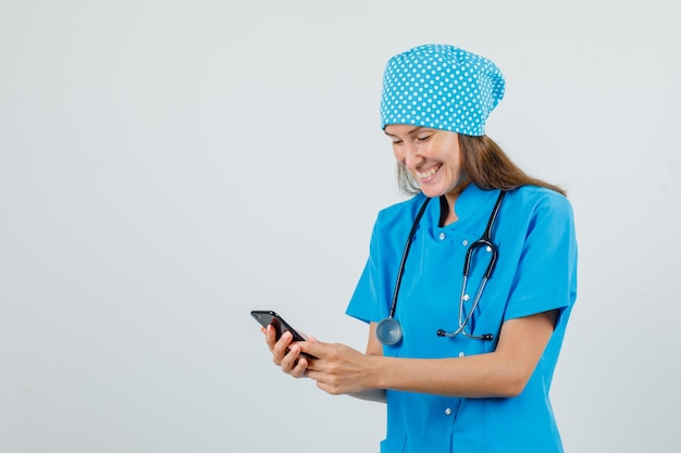 Женщина-врач в синей форме с помощью смартфона и улыбается