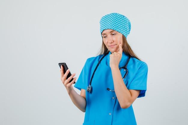 Женщина-врач в синей форме с помощью смартфона с пальцем на щеке и мечтательный вид спереди.