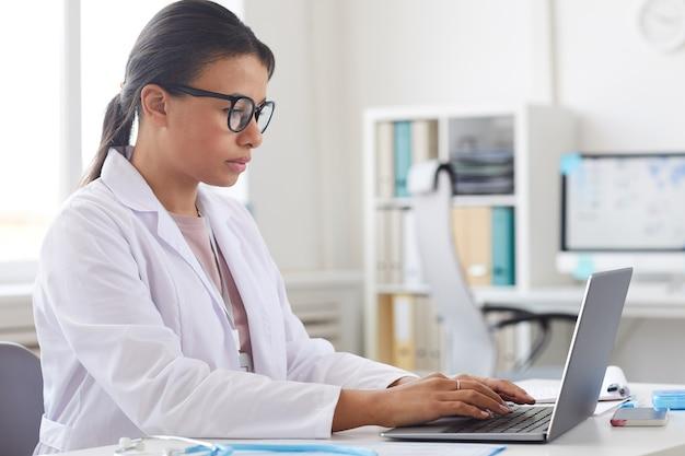 Женщина-врач в очках и в белом халате сидит за столом и концентрируется на своей работе на портативном компьютере