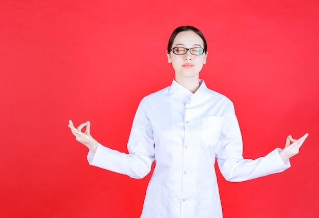 赤い背景の上に立って瞑想をしている眼鏡の女性医師。
