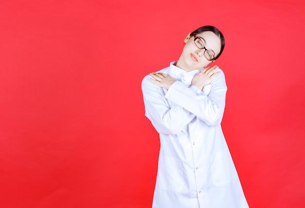 빨간 배경에 서서 피곤하고 졸린 느낌의 안경을 쓴 여성 의사.