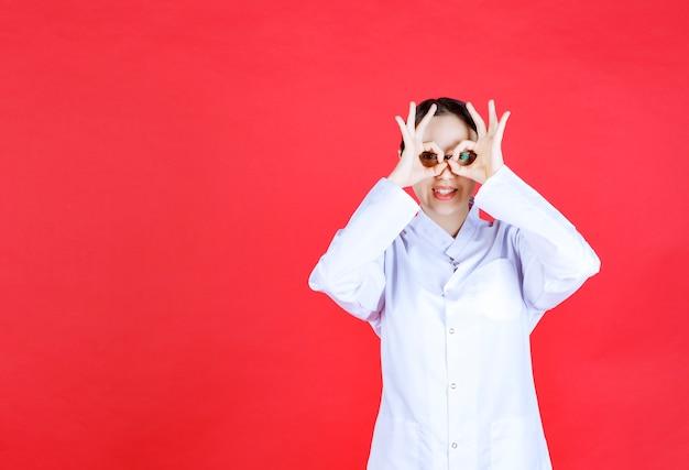안경을 쓴 여성 의사는 빨간색 배경에 서서 손가락을 가로질러 보고 있습니다.