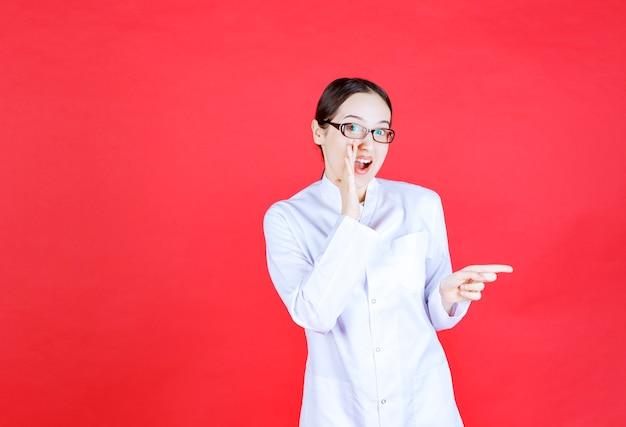 赤い背景の上に立って、右側を示している眼鏡の女性医師。