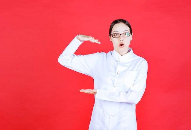 안경을 쓴 여성 의사는 빨간색 배경에 서서 물체의 크기를 보여줍니다.