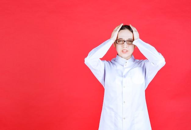 手で頭を保持し、おびえているように見える赤い背景の上に立っている眼鏡の女性医師。