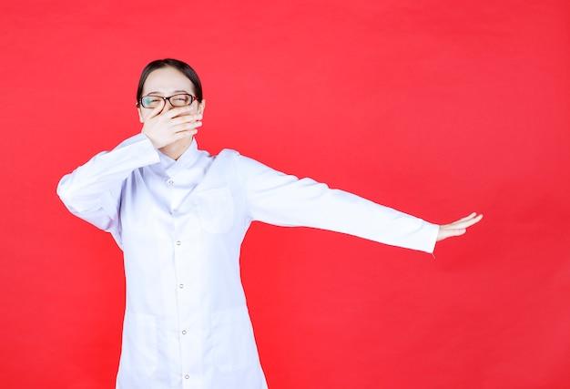 나쁜 냄새를 방지하기 위해 코를 잡고 빨간색 배경에 안경에 여성 의사.