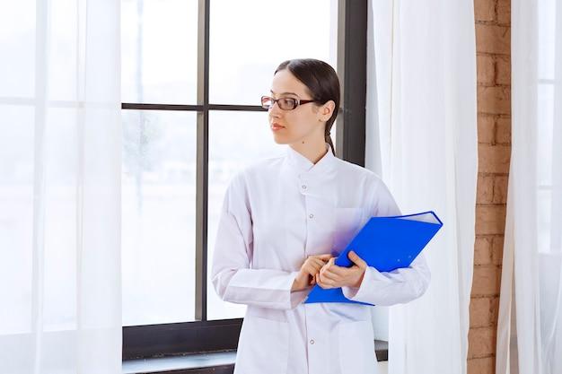 Женщина-врач в очках, держа синюю папку возле окна.