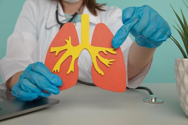 장갑을 낀 여성 의사는 폐 모델이 초기 진단의 중요성이라는 개념을 보여줍니다