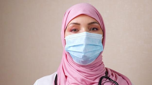 首の周りに電話内視鏡と顔にマスクを持つヒジャーブの女性医師