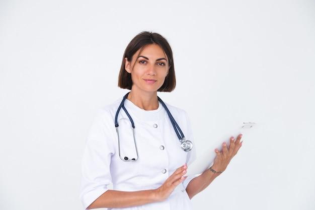 흰색 절연, 자신감이 미소에 실험실 코트에서 여성 의사 잡고 백서 빈