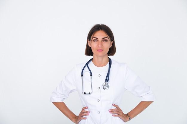 흰색 절연, 자신감 미소에 실험실 코트에서 여성 의사