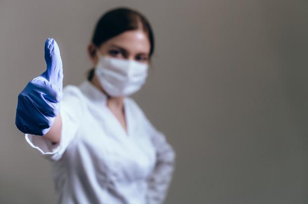 医療ガウンと手に医療用手袋の女医が親指ジェスチャーを示しています