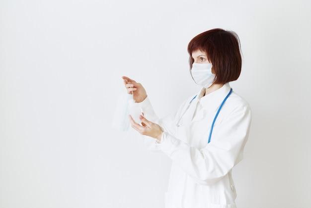 Женщина-врач в медицинской маске и униформе предлагает маску и дезинфицирующее средство в бутылке