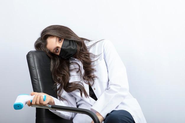 Женщина-врач в медицинской маске, держащей термометр и сидя на стуле.