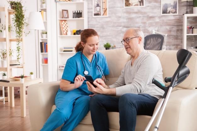 요양원의 여성 의사가 전화를 사용하는 노인을 돕고 있습니다.